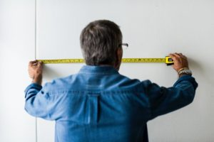 Man Measuring wall using Tape