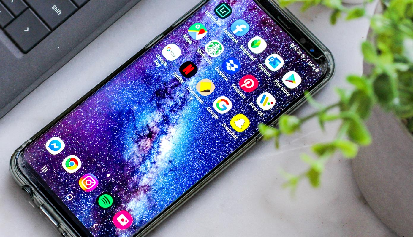 Android Mobile with Apps Display Near Laptop