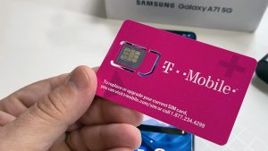 T-Mobile SIM card in Hand with Samsung A71 5G in Background