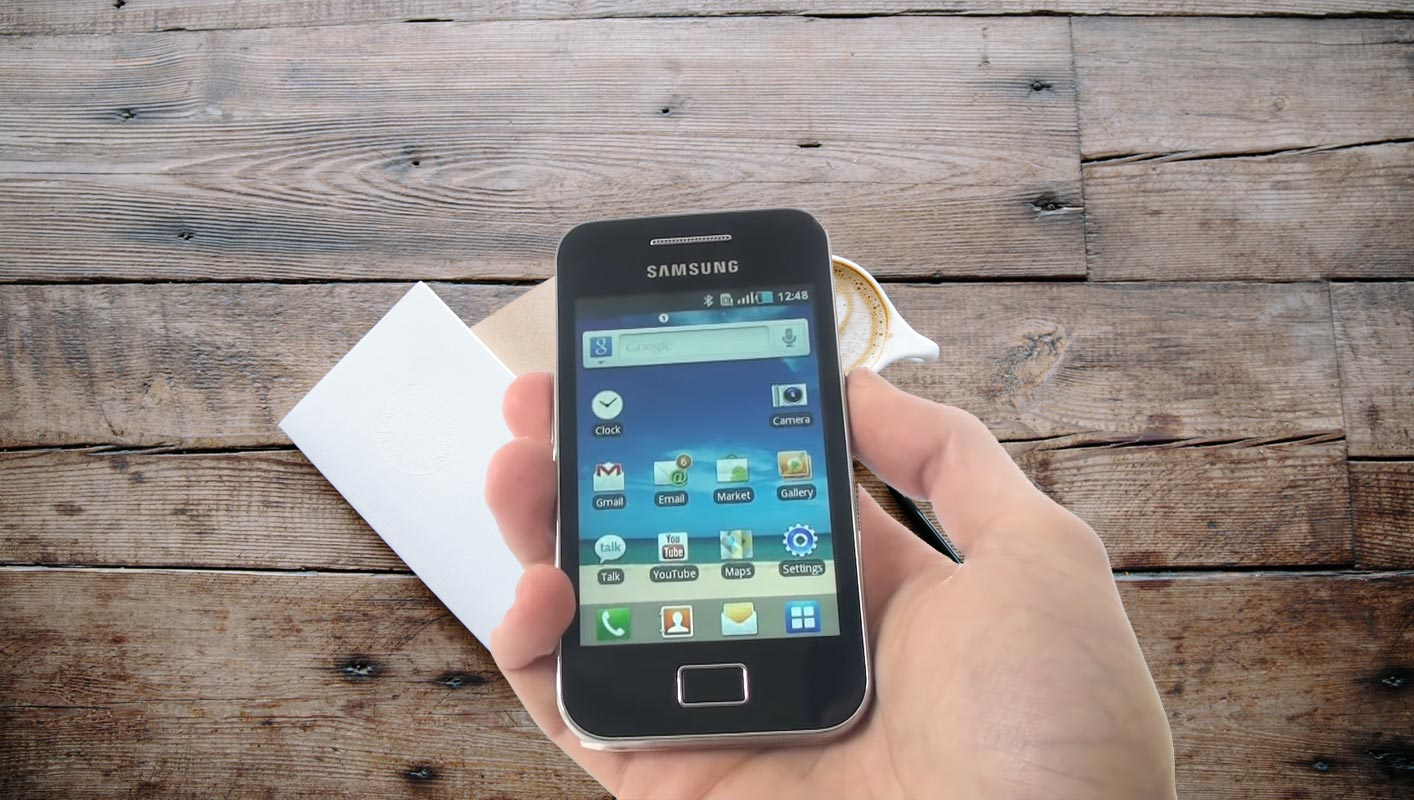 Samsung Galaxy Ace mobile Home Screen in hand